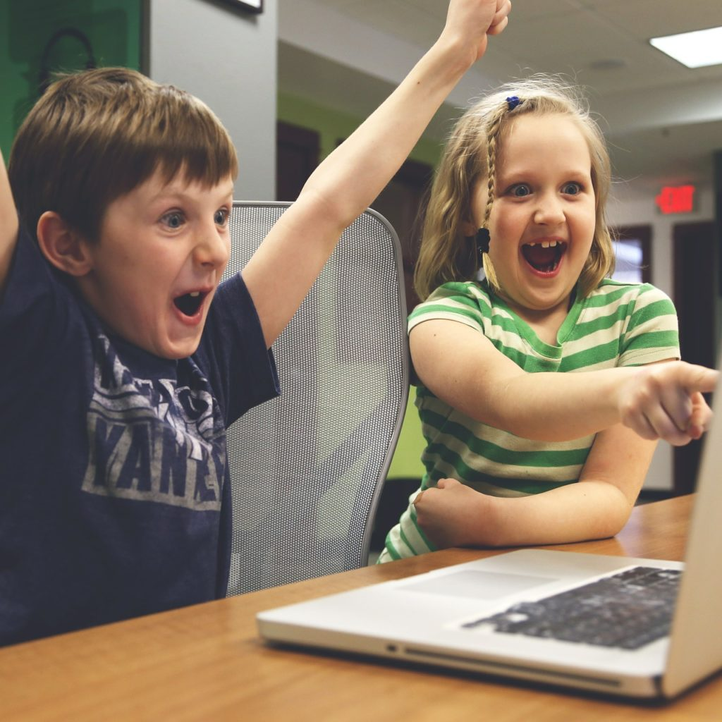 excited kids using a laptop